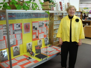 Vonda Pelto in front of display case qt library with her book, Without Remrose, about her time dealing with serial killers as a budding psychologist.