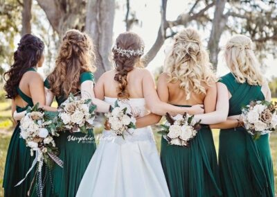 Portrait of bride with bridesmaids from behind. Image by Umphie Photos.