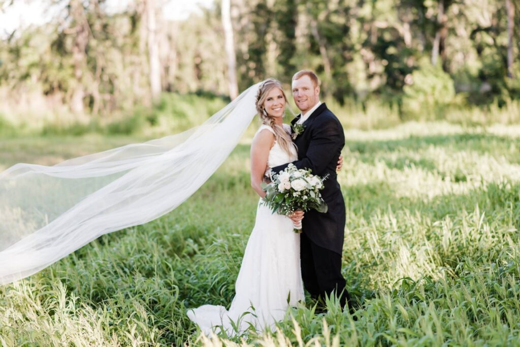 This bride requested an area of grass to be left high and uncut, specifically for photos like this one. The shadows, the color variations of the foliage and her veil lifting in the breeze combined for an unforgettable photo by AmberDornPhotography.com.