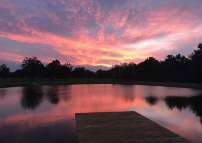 The view of sunset from the dock in front of the C Bar Ranch events barn often will leave you mesmerized. Vivid colors paint the sky, with trees in silhouette in the distance.