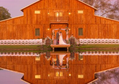 The barn front reflects into the pond, creating a mirror image and an unforgettable wedding portrait location. Image by thereflectionsstudio.com.