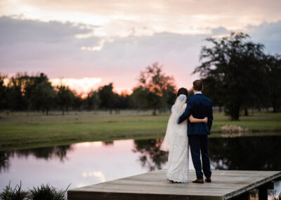 Couple faces the sunset on the dock by Amber Dorn Photography