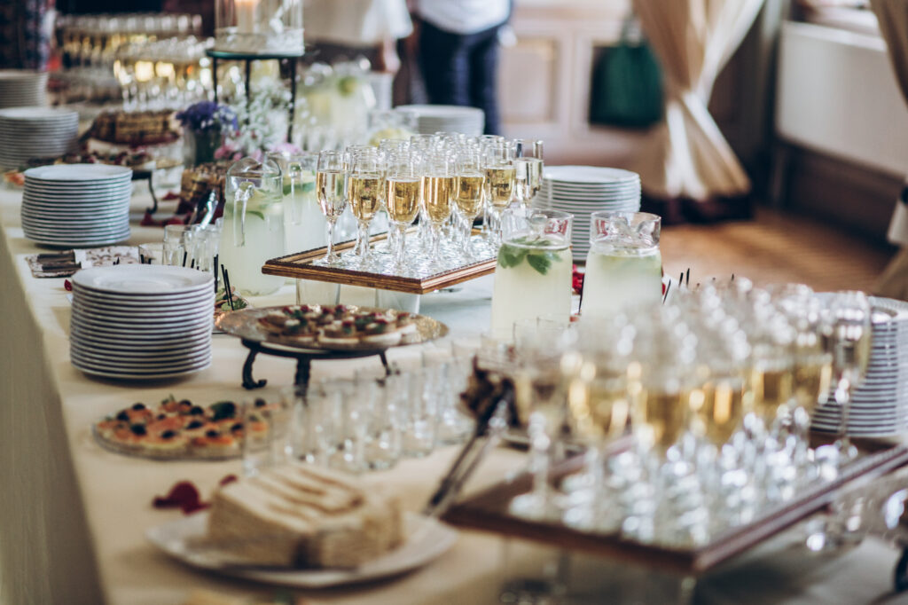 stylish champagne glasses and food  appetizers on table at wedding reception. luxury catering at celebrations. serving food and drinks at events concept