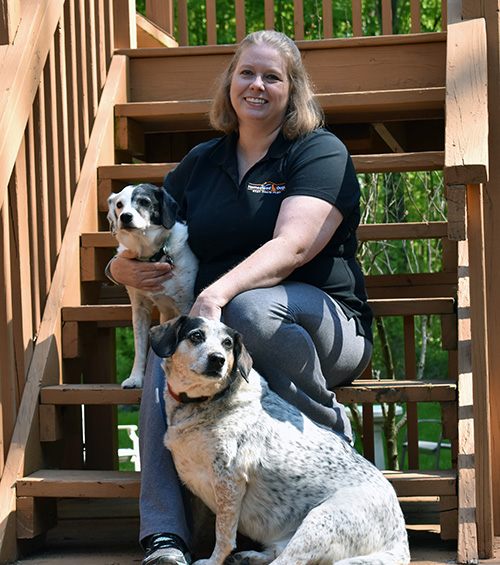 A picture of Amy sitting on the stairs with her two dogs.