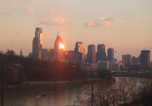 Philadelphia skyline from train, reflecting sun.