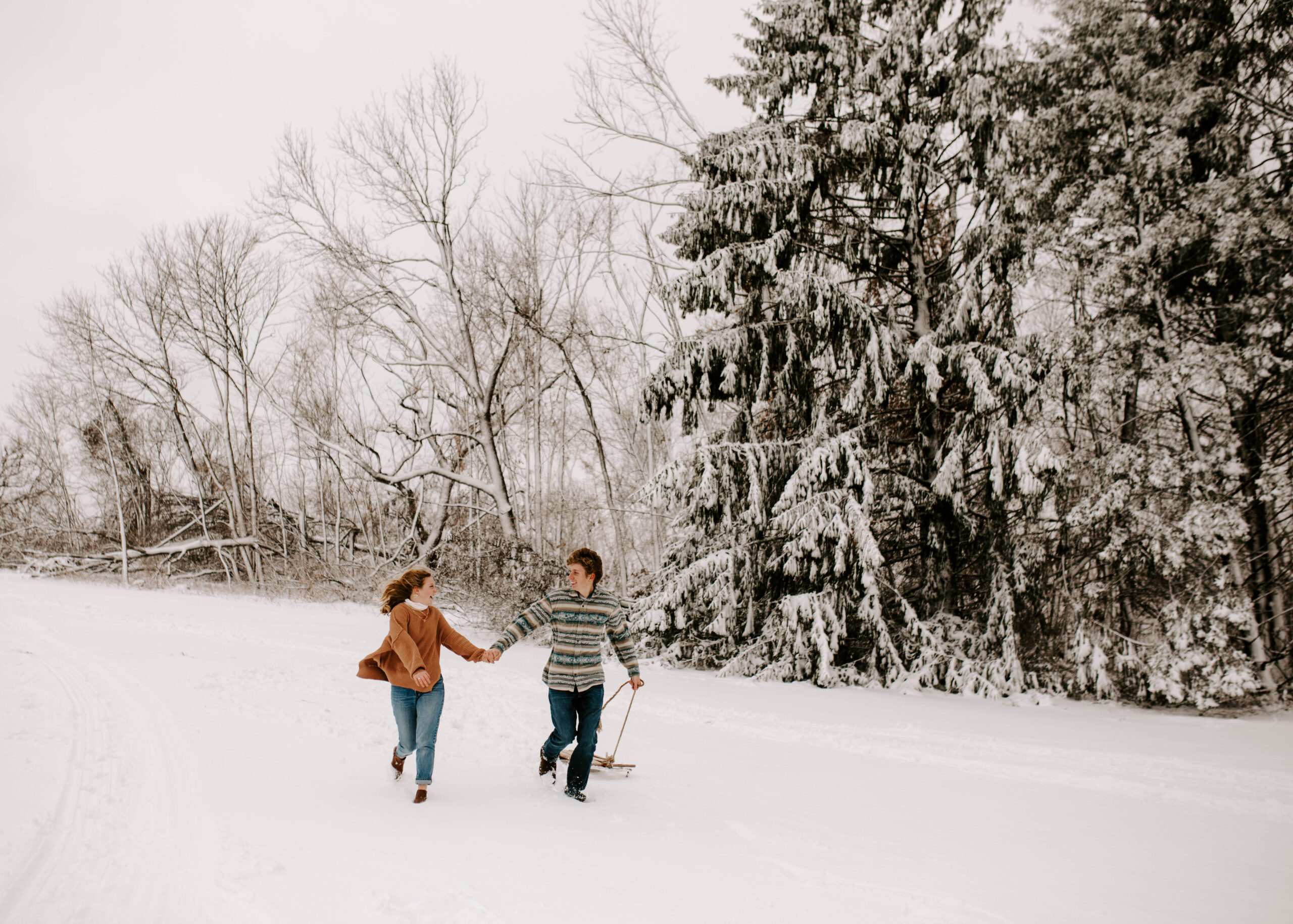 Iowa Winter Snowy Engagement Session, Couple runs through the snow with a sled