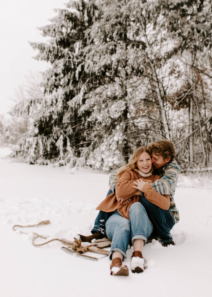 Iowa Wedding Photographer, couple snuggles up on sled after a big snow