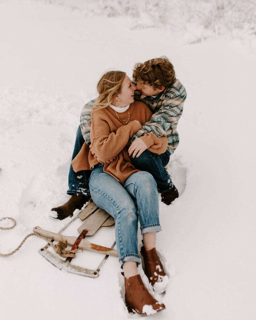 Iowa Wedding Photographer, couple snuggles up on a sled after a big snow