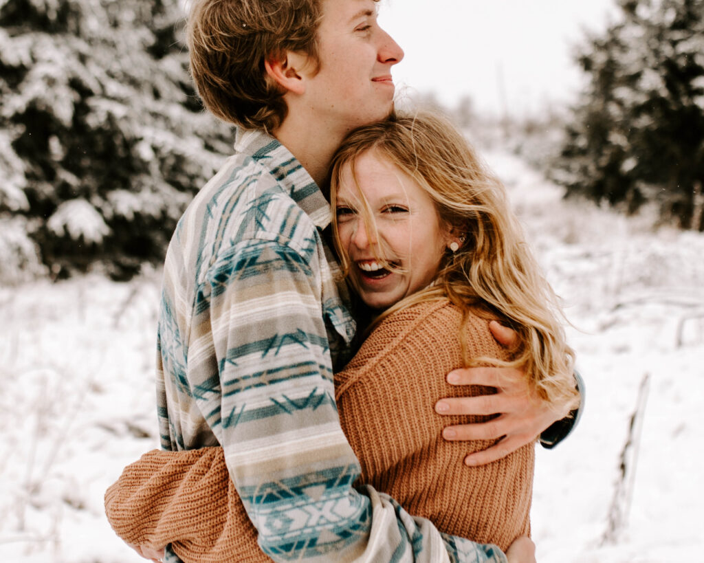 Iowa Wedding Photographer, Couple hugs and smiles in the snow during their winter engagement session