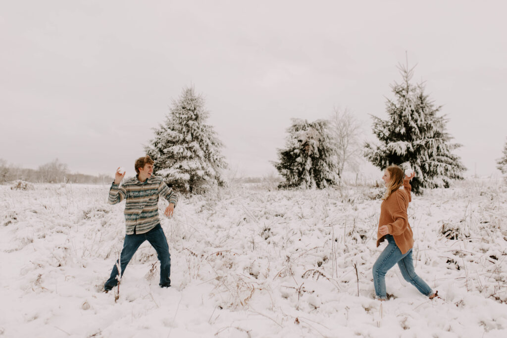Iowa engagement session in the winter, couple has a snowball fight