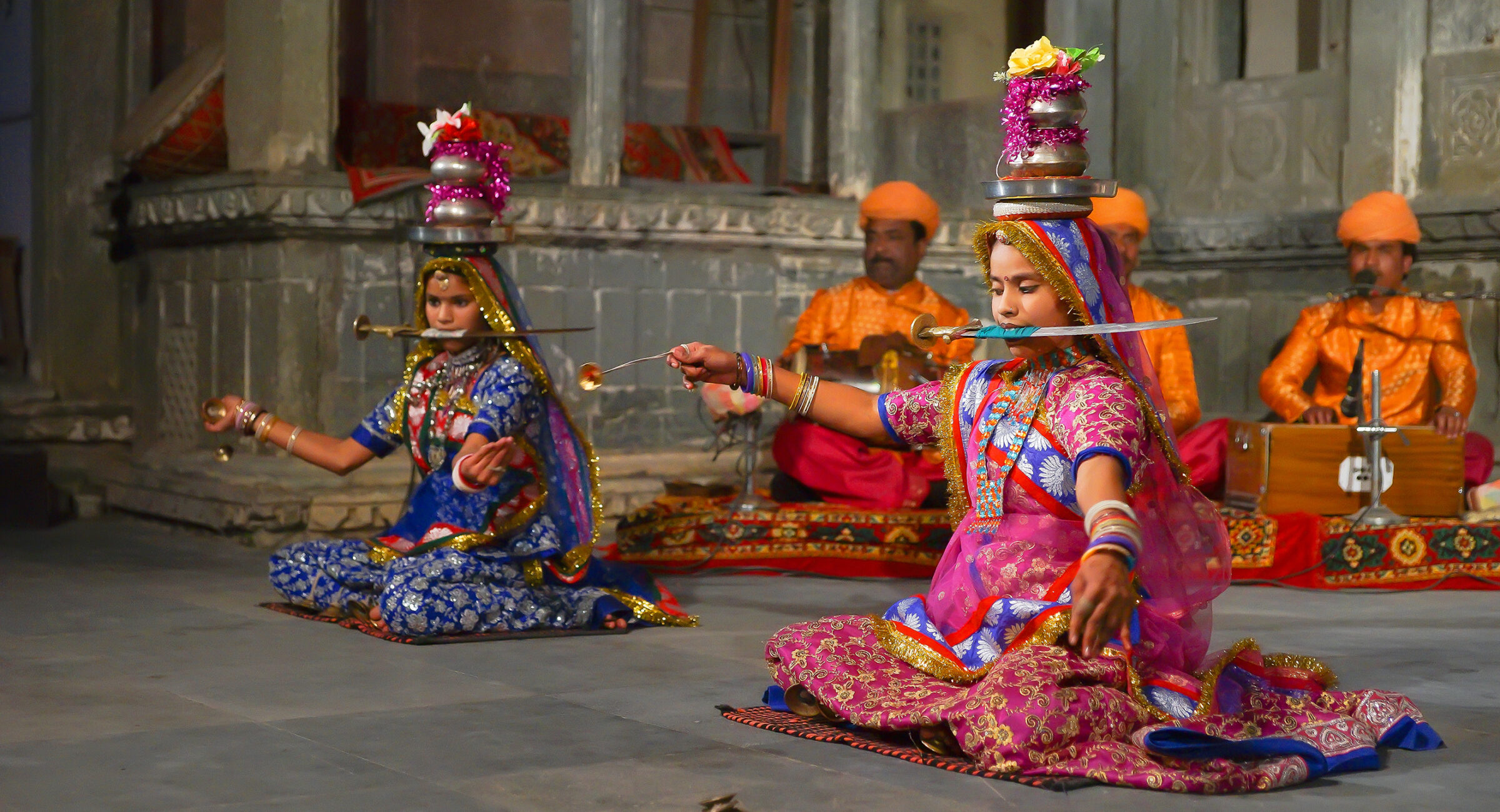 Udaipur, India - JanuaryY 29, 2014: An unidentified young indian women in sari perform dance with knifes, small metal plates and pots on heads at a traditional festival exposing local Rajasthan culture in Udaipur, India