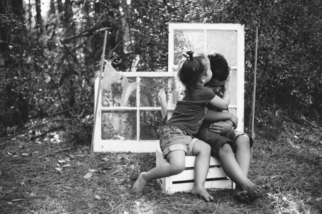 siblings kiss black and white