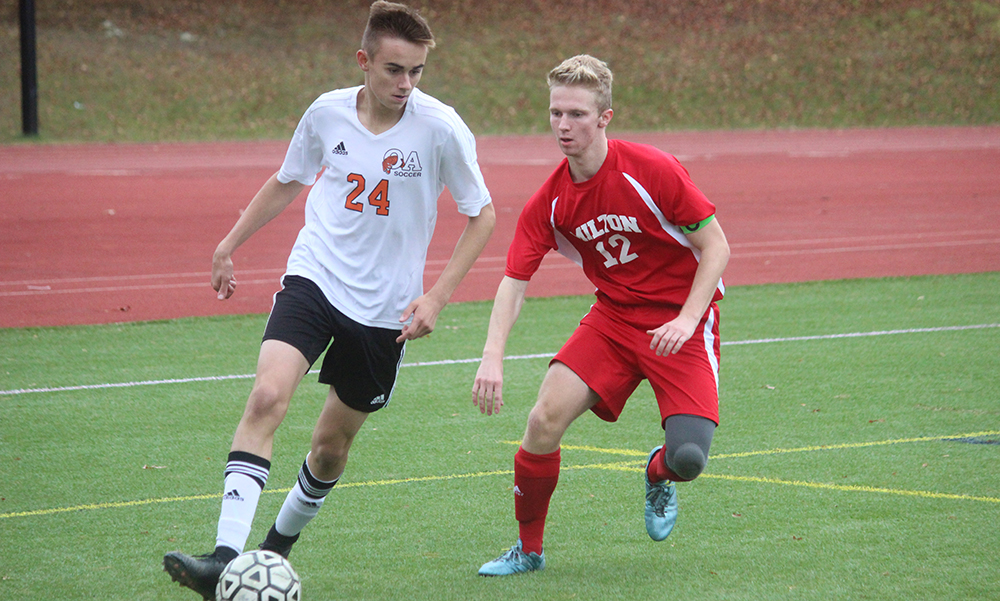 Oliver Ames' Cam Vella dribbles around Milton's Cole Kroninger in the first half at Mustaco Stadium. (Ryan Lanigan/HockomockSports.com)