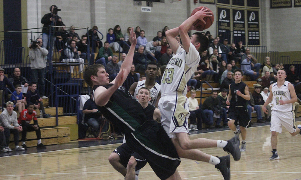 Foxboro's Alex DuBrow (right) attempts a shot over Mansfield's Kyle Swansburg in the first half. (Ryan Lanigan/HockomockSports.com)