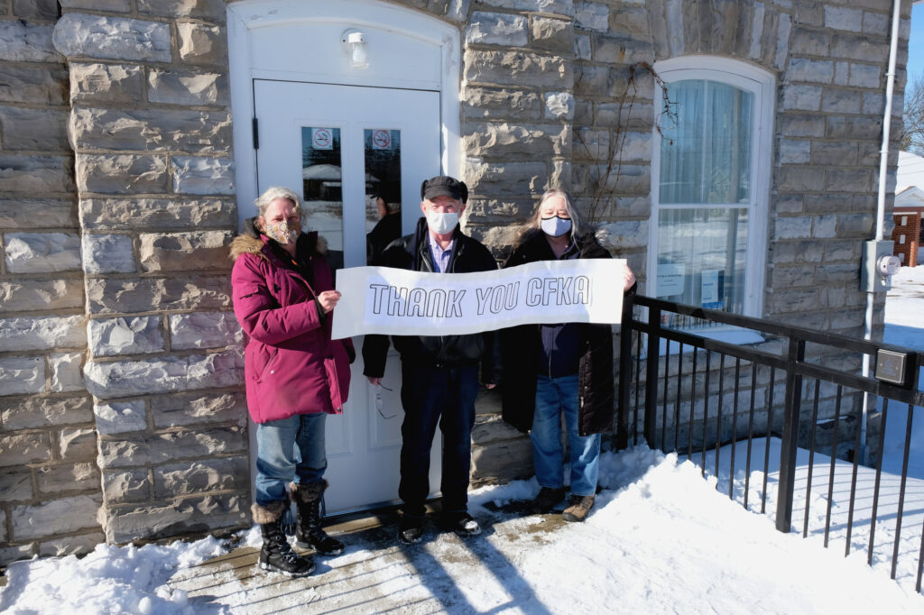 Three museum members holding a thank you sign outside the museum in the winter