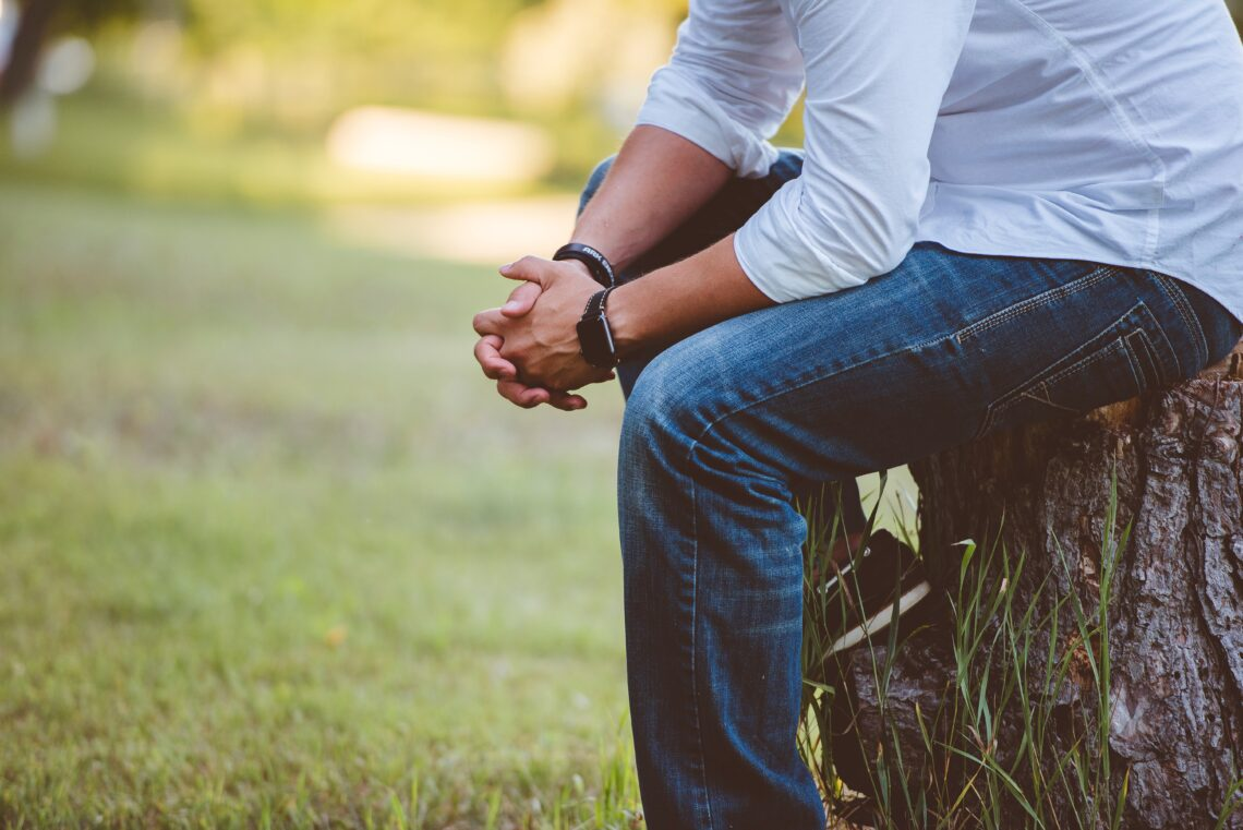 man sitting on tree stump with clasped hands
