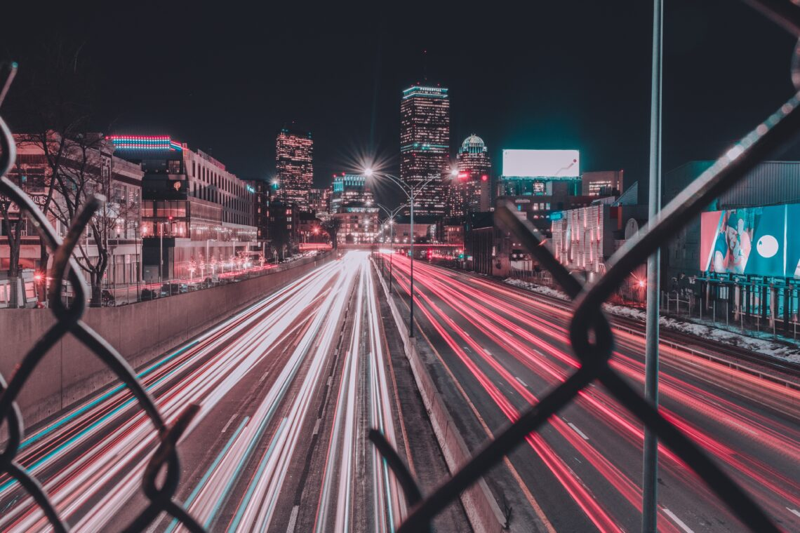 time lapse of city highway through fence