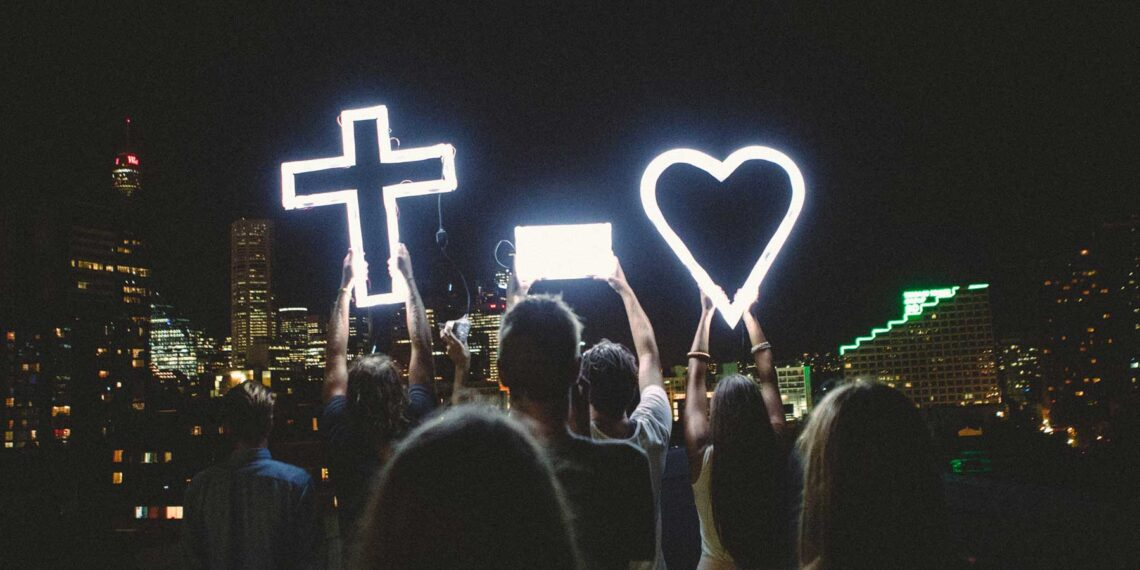photo of crowd holding lighted 'cross equals love' signs against nighttime city metro background