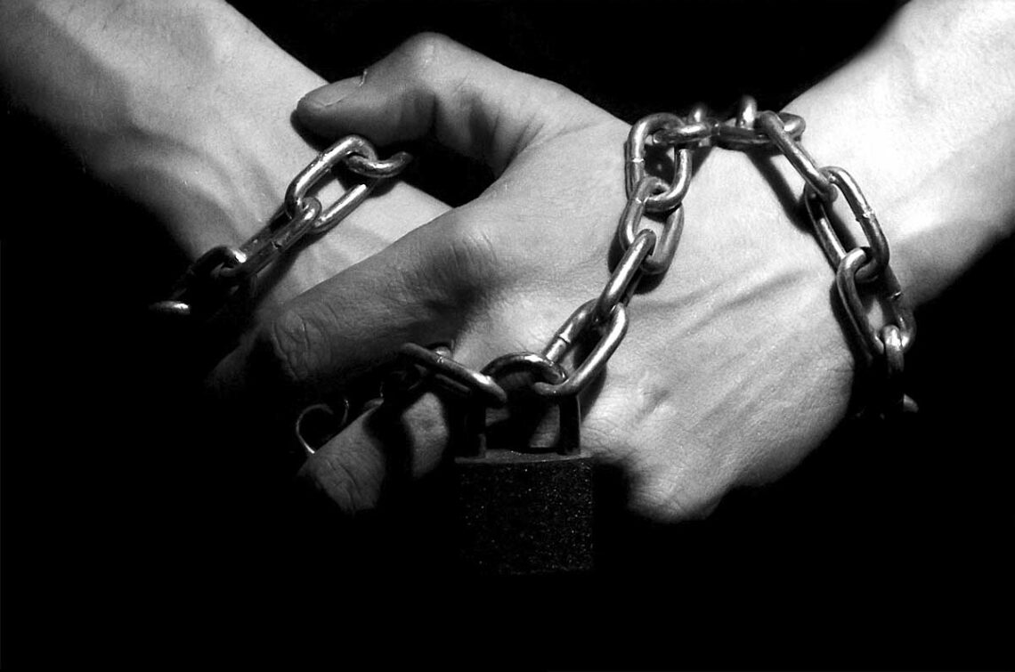 photo of clasped hands in chains