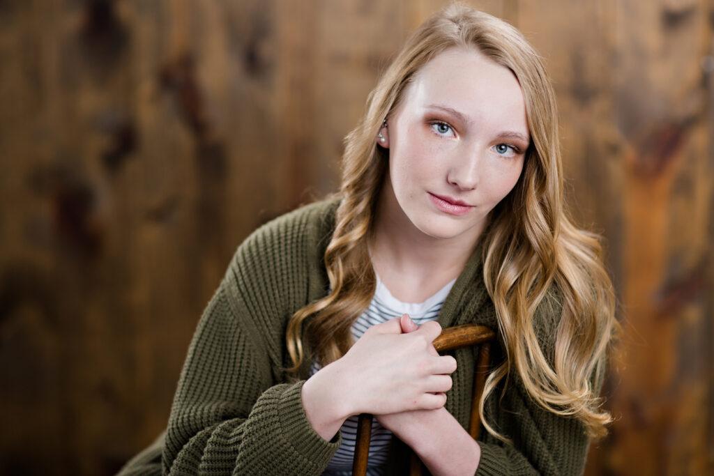 In studio senior portrait on wood background.