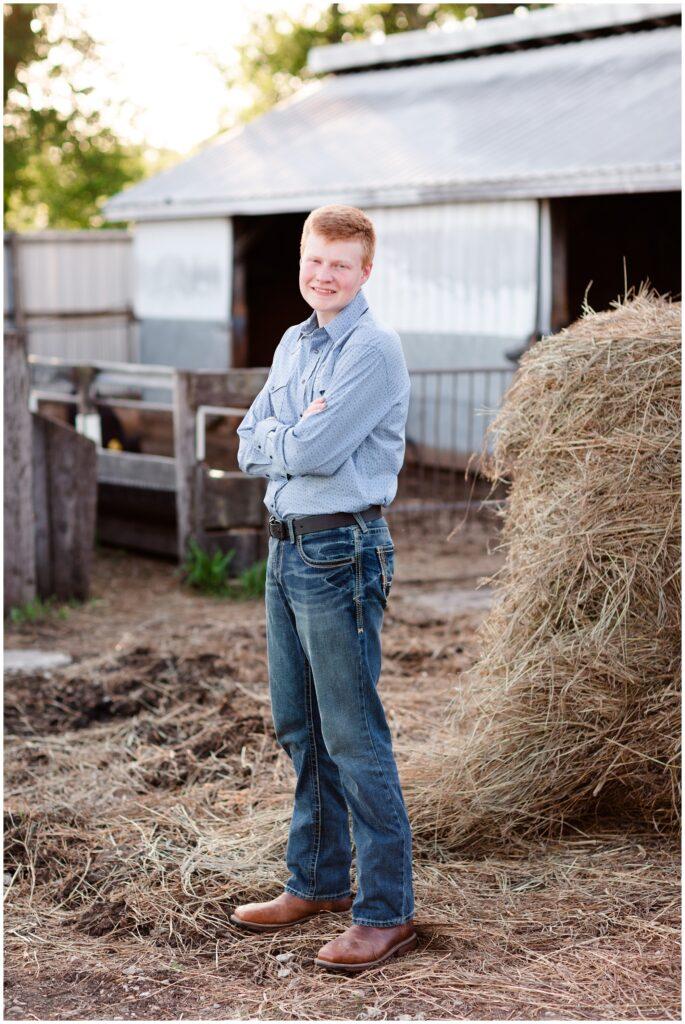 Senior photo on hay bales and cattle cows | Farm senior session | Iowa Senior Photographer | CB Studio