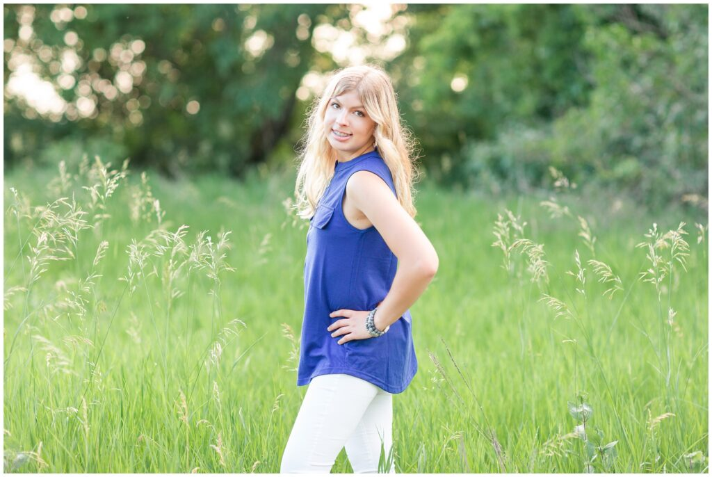 Senior portrait session at a park during golden hour | Senior girl poses in a grassy field | Iowa Senior Photographer | CB Studio