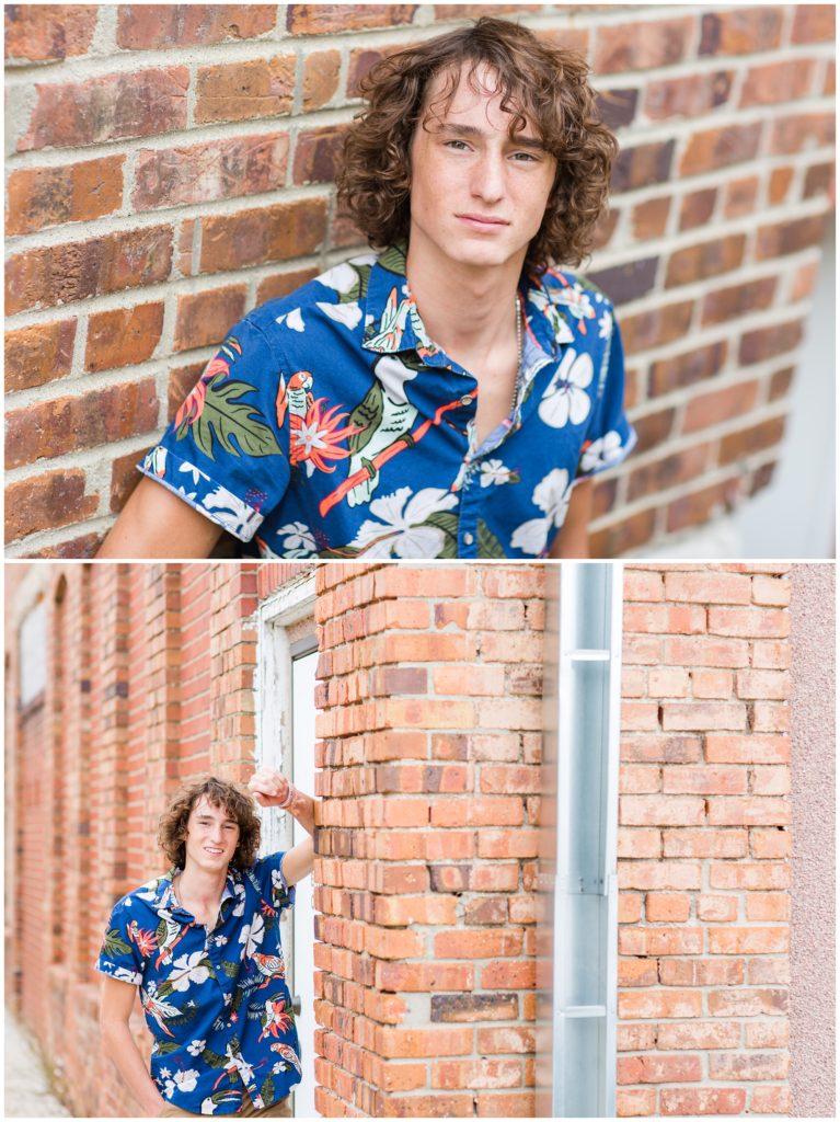 Senior boy poses along a brick wall in downtown Algona, IA CB Studio Photography