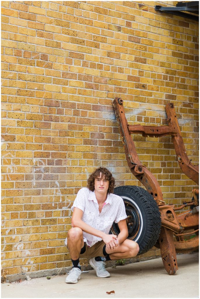 Senior boy poses squatting by an old rusty wheel base and brick wall in downtown Algona, IA CB Studio Photography