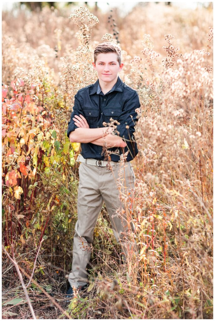 Fall senior boy session standing in a grassy field | Iowa Senior Photographer | CB Studio