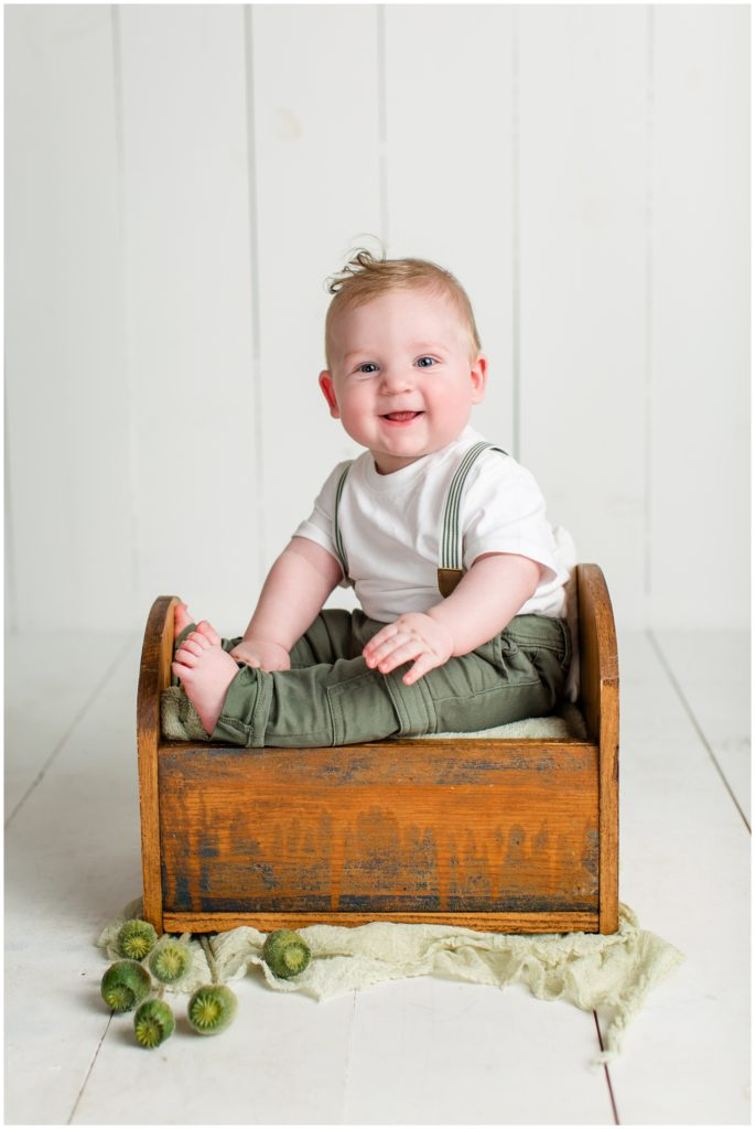 6 month old baby boy sitting in a small wooden baby bed wearing suspenders with a little bit of greenery in the decor | Sitter Session | Iowa Baby Photographer | CB Studio