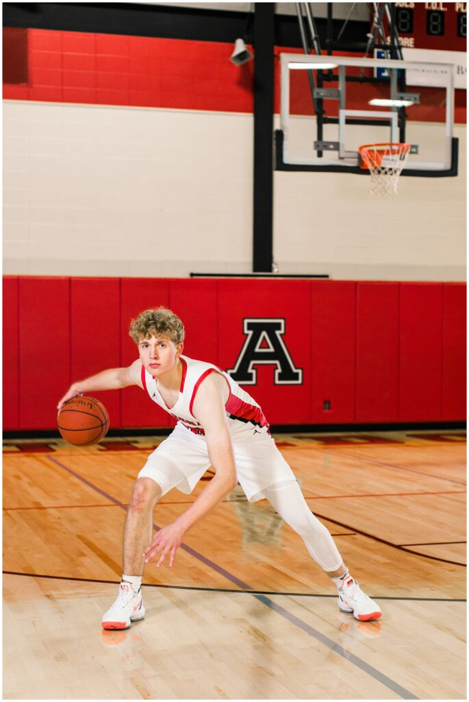 Senior boy dribbling a basketball in the Algona High School gym | Iowa Senior Photographer | CB Studio