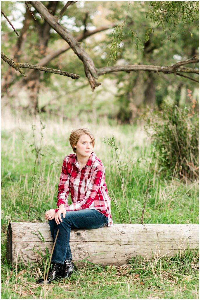 Senior poses in a grassy field | Iowa Senior Photographer | CB Studio