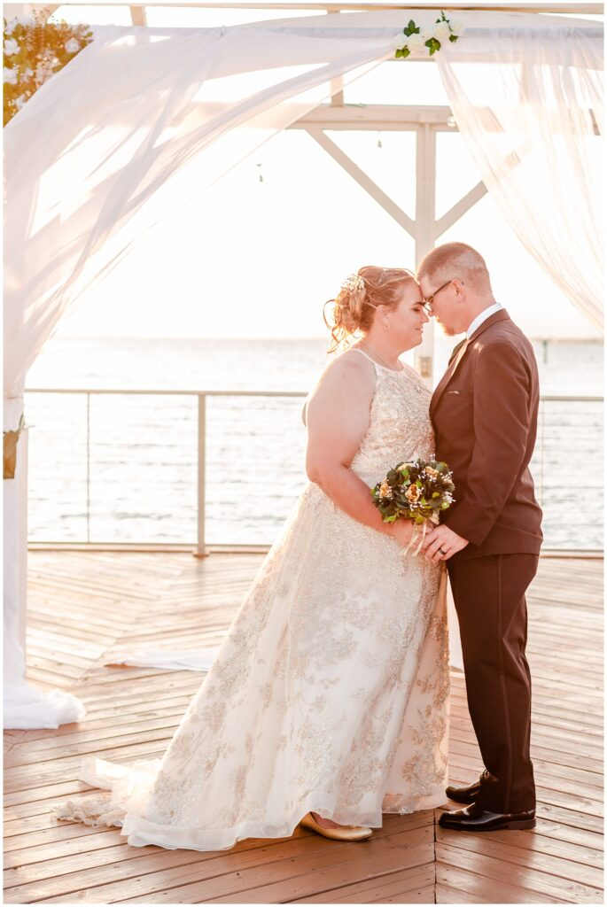 Bride and groom romantically standing under a white wedding pergola with white drapes flowing in the breeze on the Godfrey Hotel bay pier over looking the bay at sunset | Tampa Bay Wedding | CB Studio