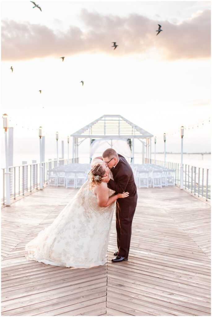 Bride and groom kissing on the pier of The Godfrey Hotel Tampa during sunset with seagulls flying over. | Tampa Bay Wedding | CB Studio