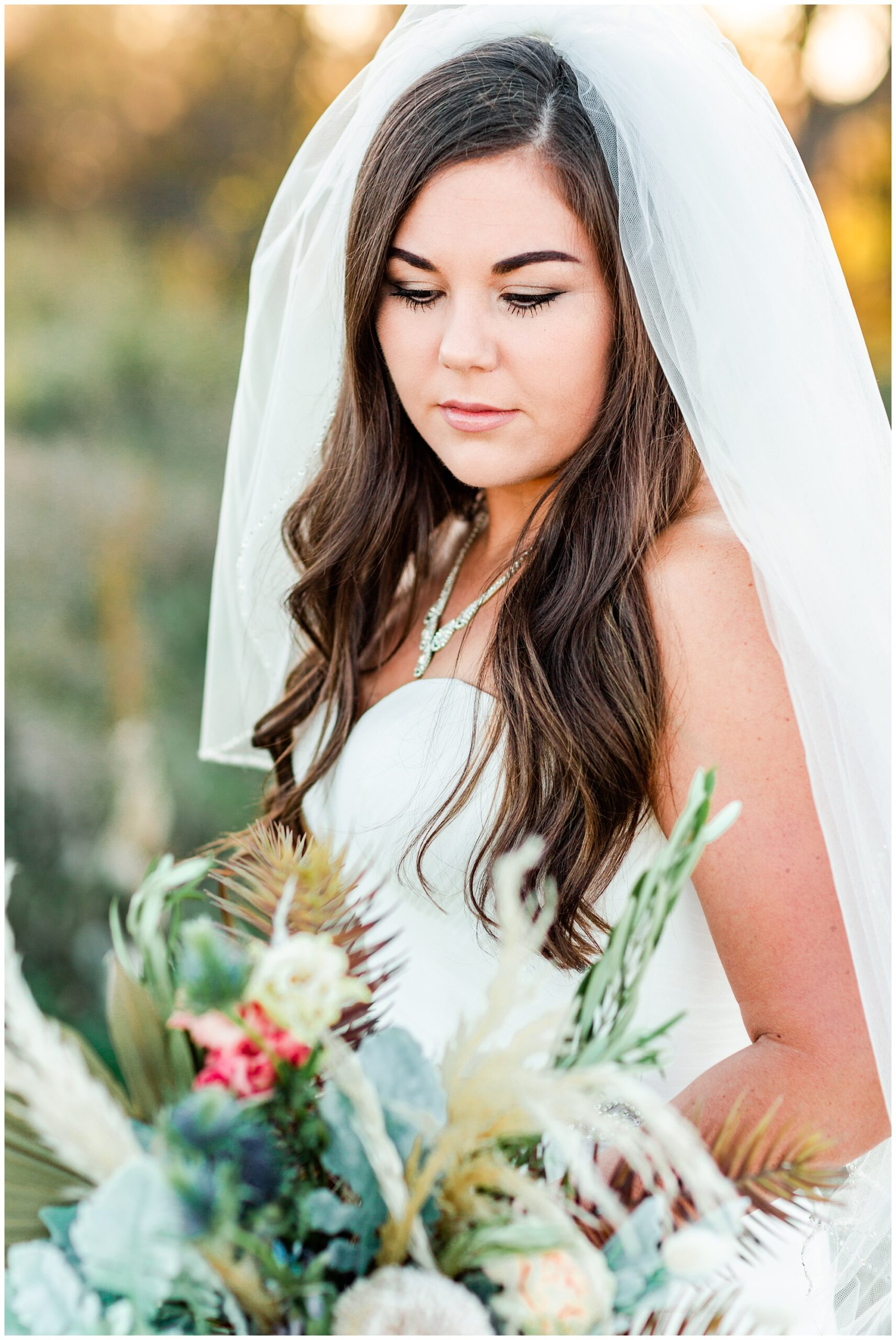 Bridal portrait looking down on a beautiful bouquet of soft florals