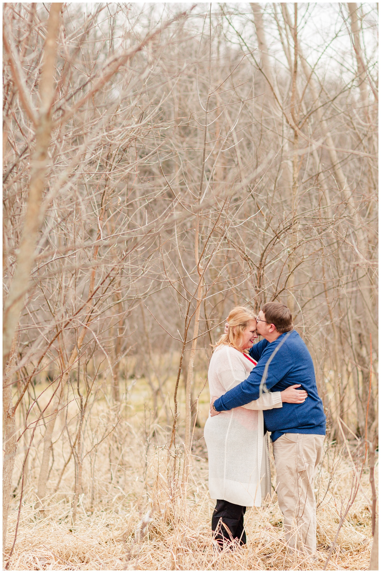 Engagement shoot in a grassy pasture in central Iowa in mid-March surrounded by trees