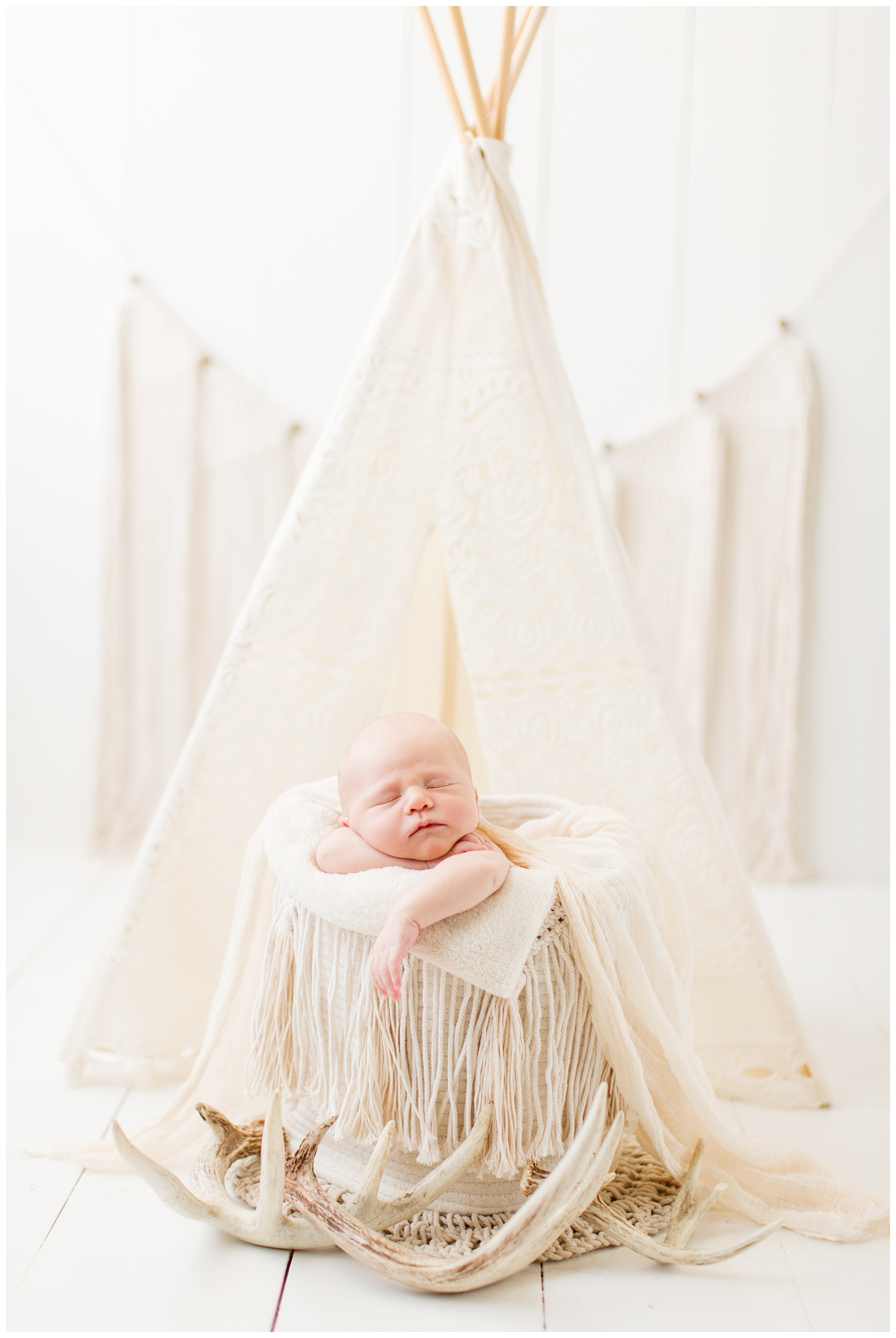 Newborn baby posing in a cream boho theme photography set up complete with deer antlers