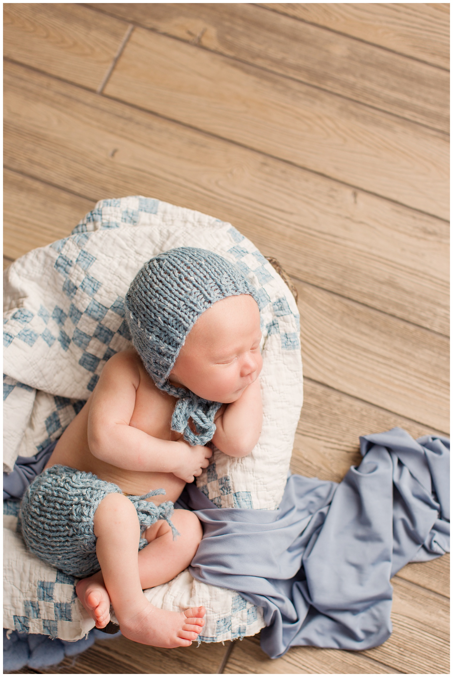 Newborn baby laying in a bowl covered with a quilt wearing a blue knit bonnet and shorts