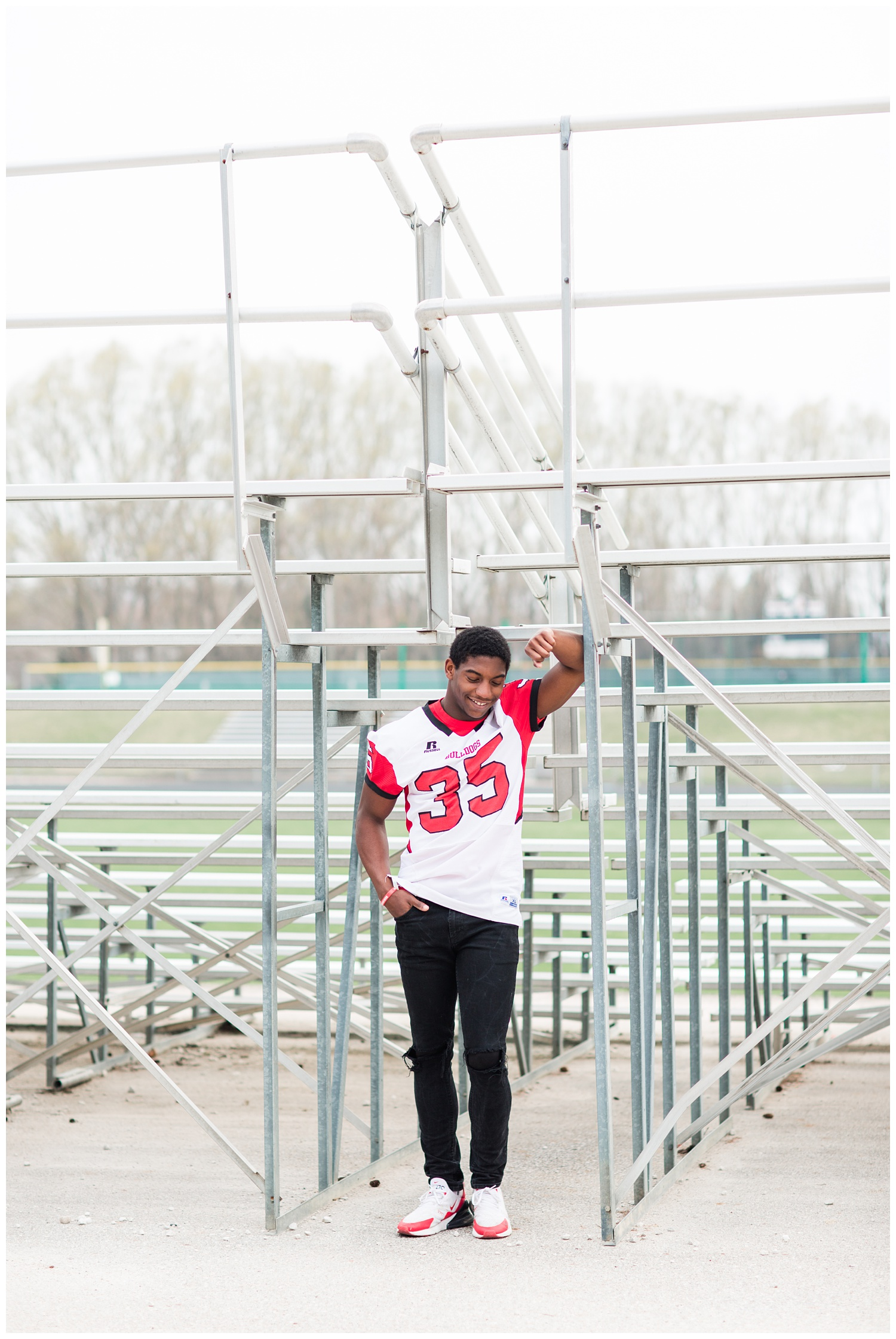 Algona senior football player leaning against the bleachers