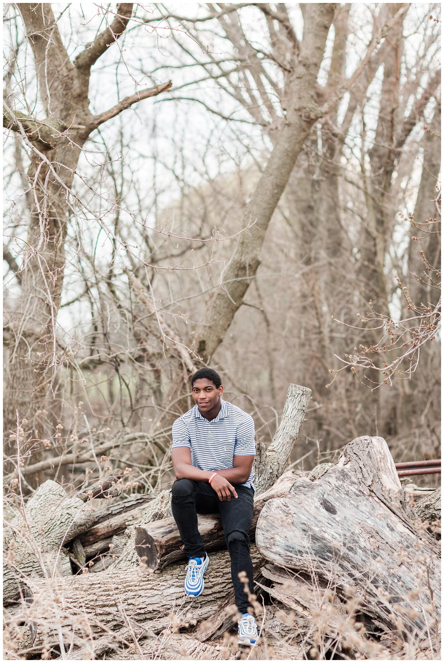 Algona high school senior posing on a pile of logs