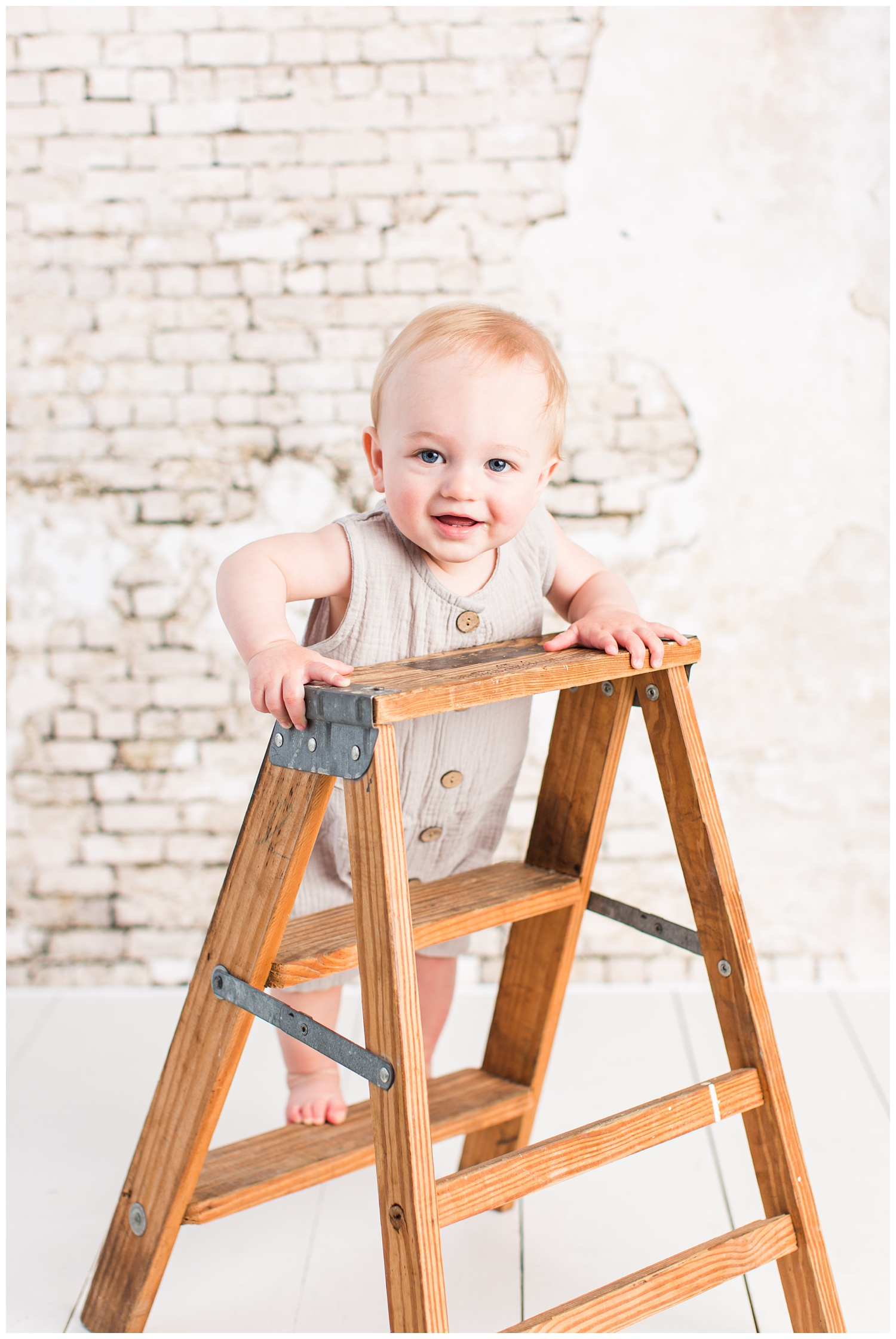 Baby Cullen poses on a wooden ladder in a gray vintage romper for his first birthday.