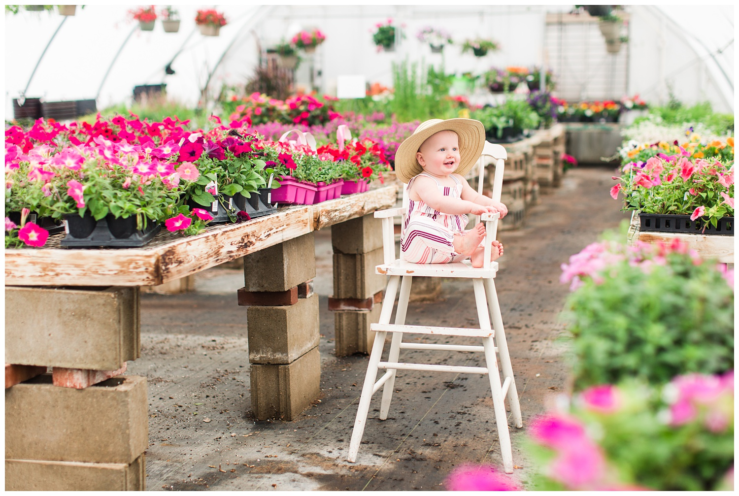 Baby Ivy sitting in a cream antique high chair surrounded by florals in a greenhouse wearing a fun floppy hat.