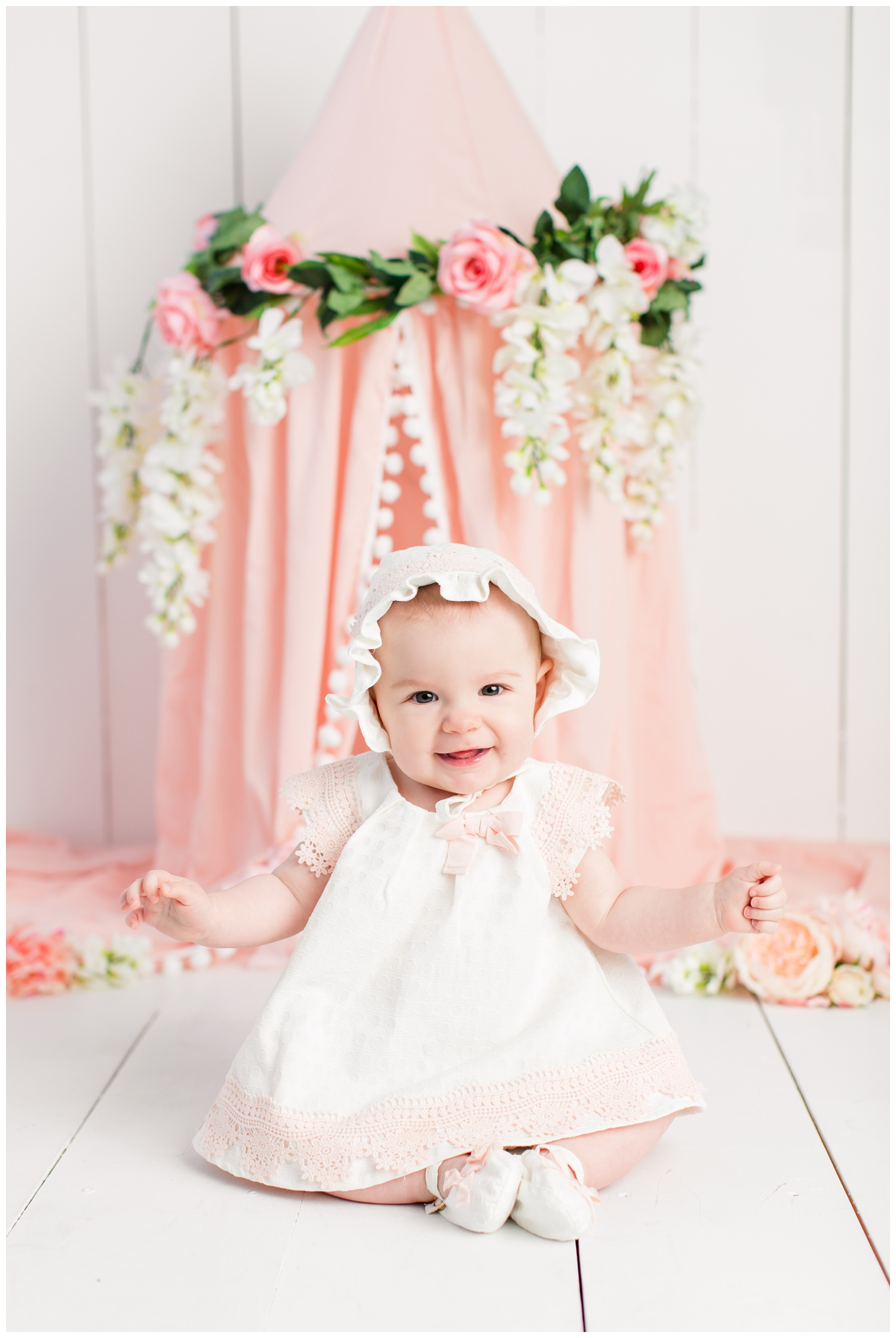 Baby Nora poses in a cream and pink babydoll dress and bonnet from TJ Maxx in front of a pink bed canopy decorated in florals.