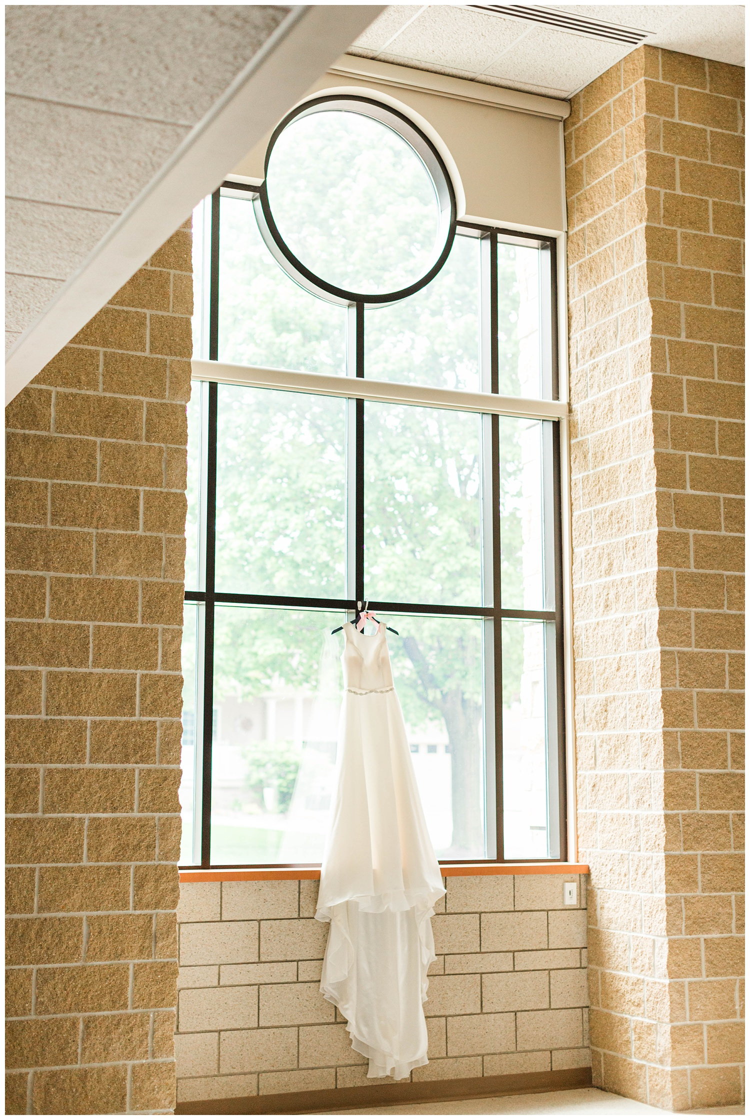 Ever London wedding dress by Justin Alexander hangs in the church window | CB Studio