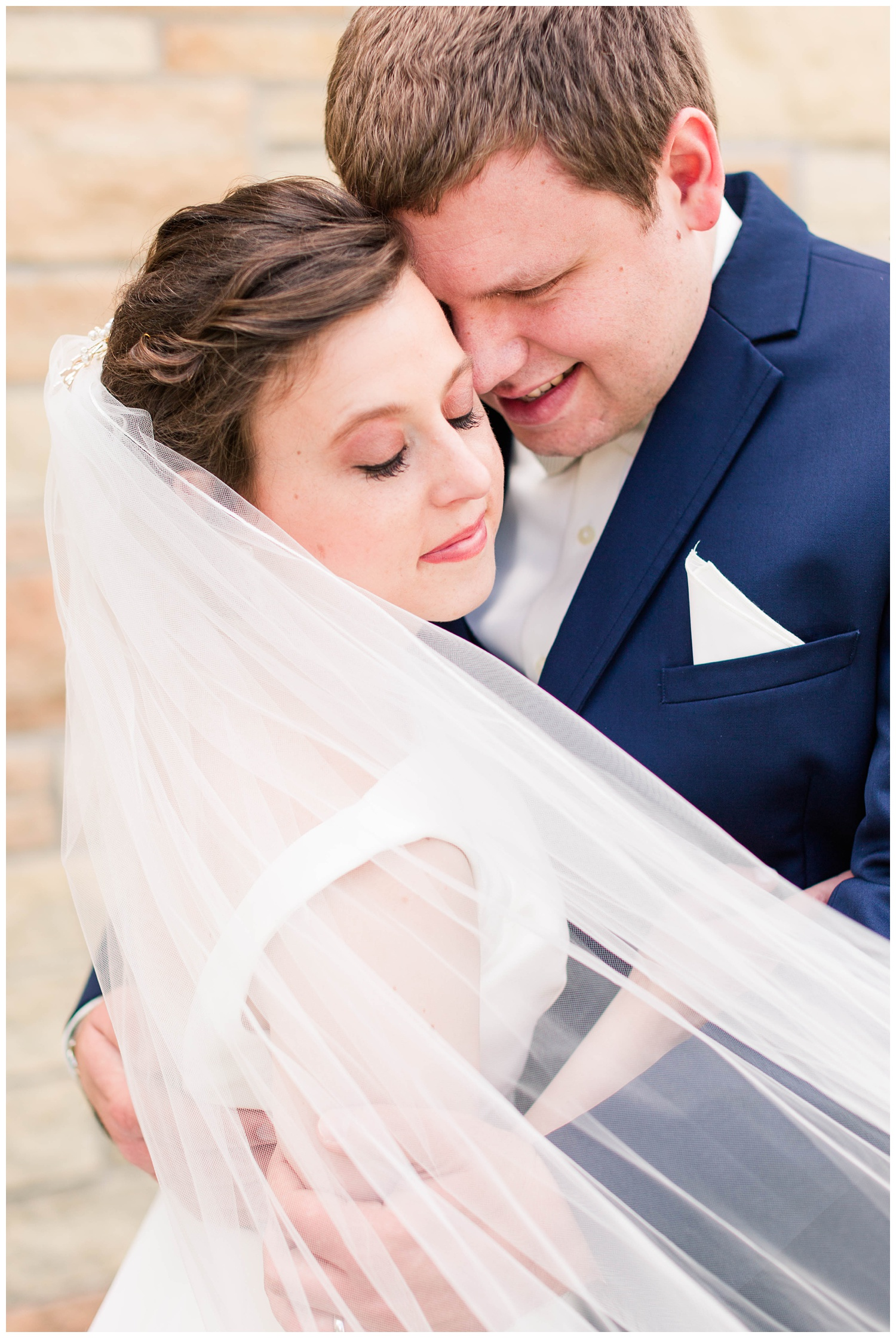 Bride and groom nuzzle in close while the veil swoops in front | CB Studio