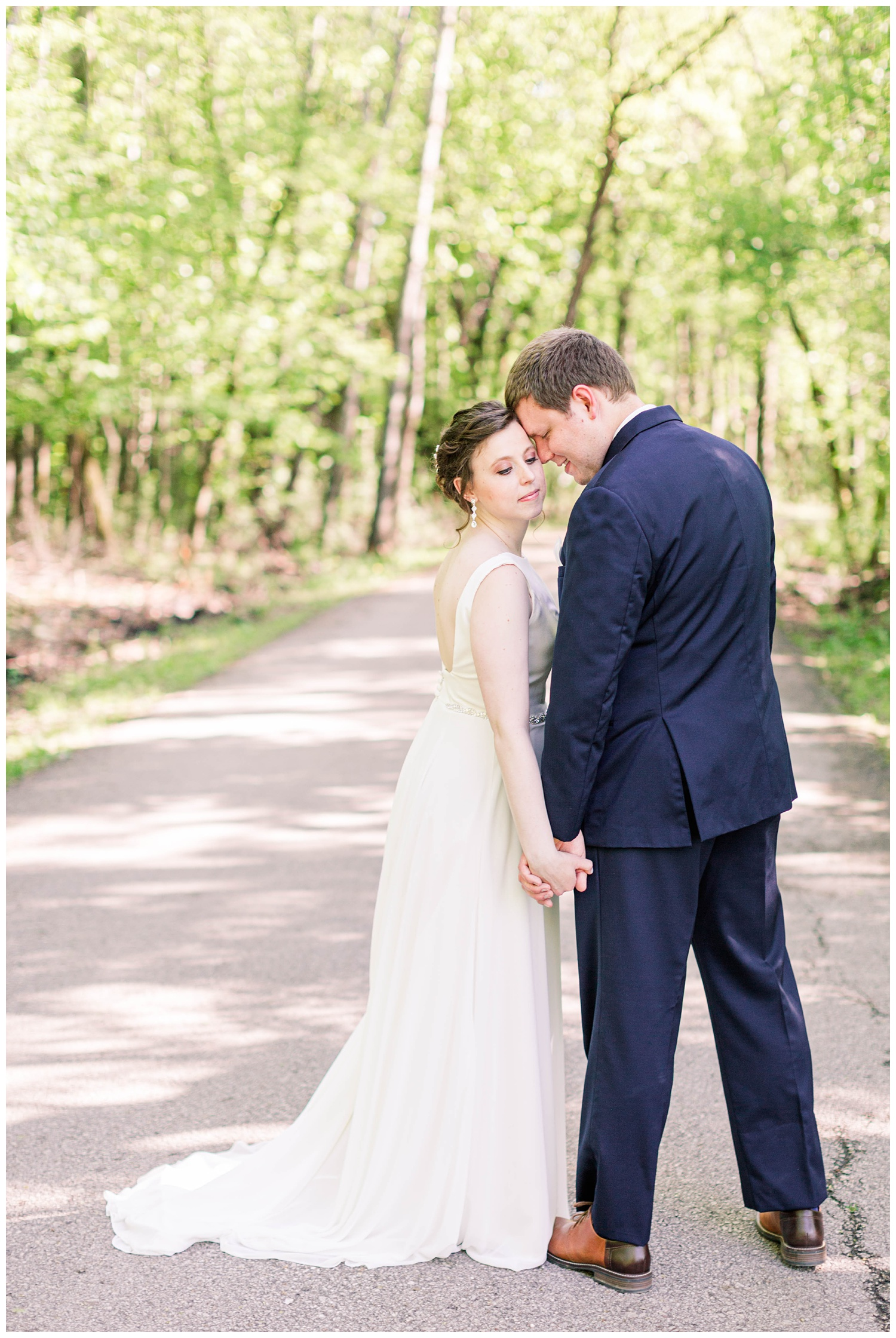 Bride and groom hold hands and nuzzle in close on a scenic path in Call Park Algona Iowa | CB Studio