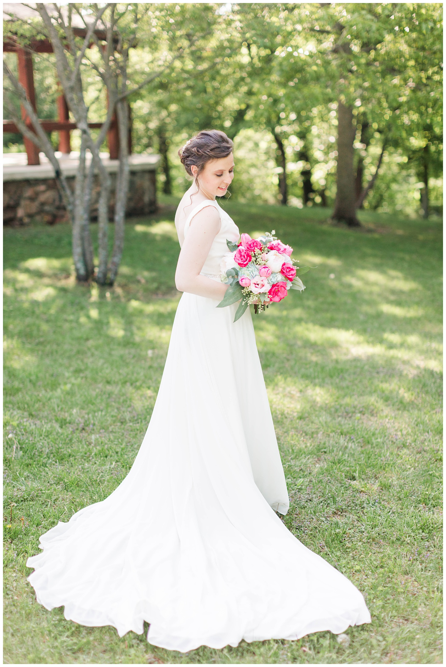 Bride wearing Justin Alexander holds white and deep pink bouquet in a scenic area of Call Park Algona Iowa | CB Studio