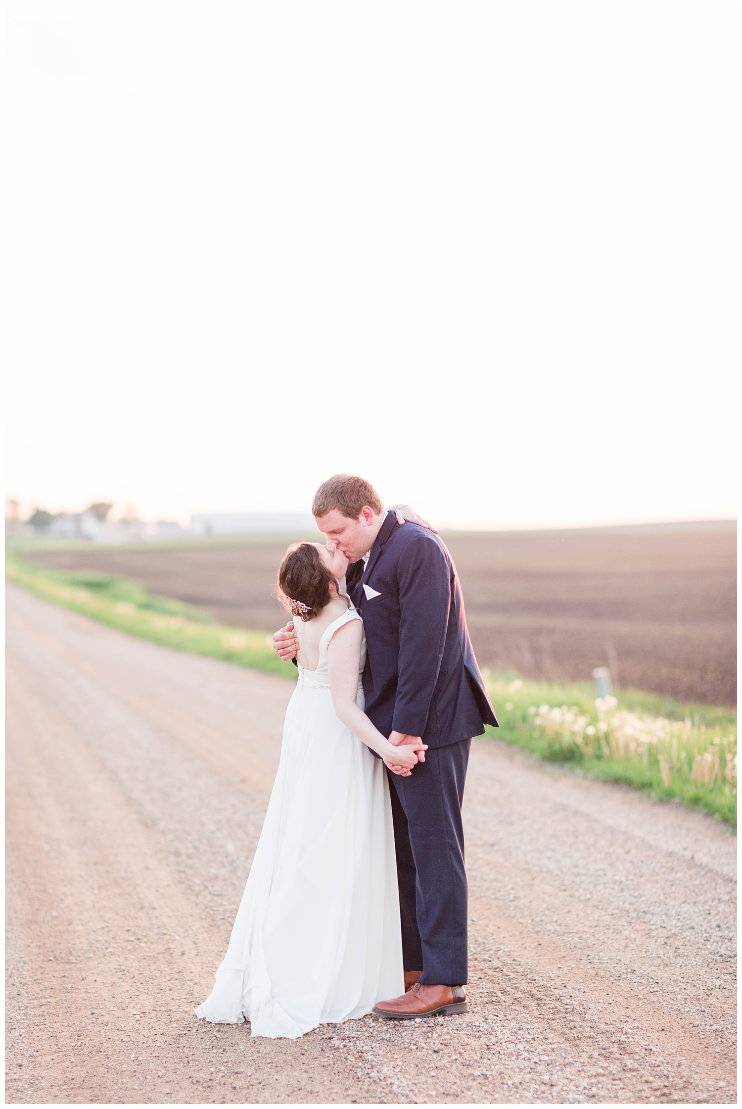Bride and groom kiss at sunset on a country road in Algona Iowa | CB Studio