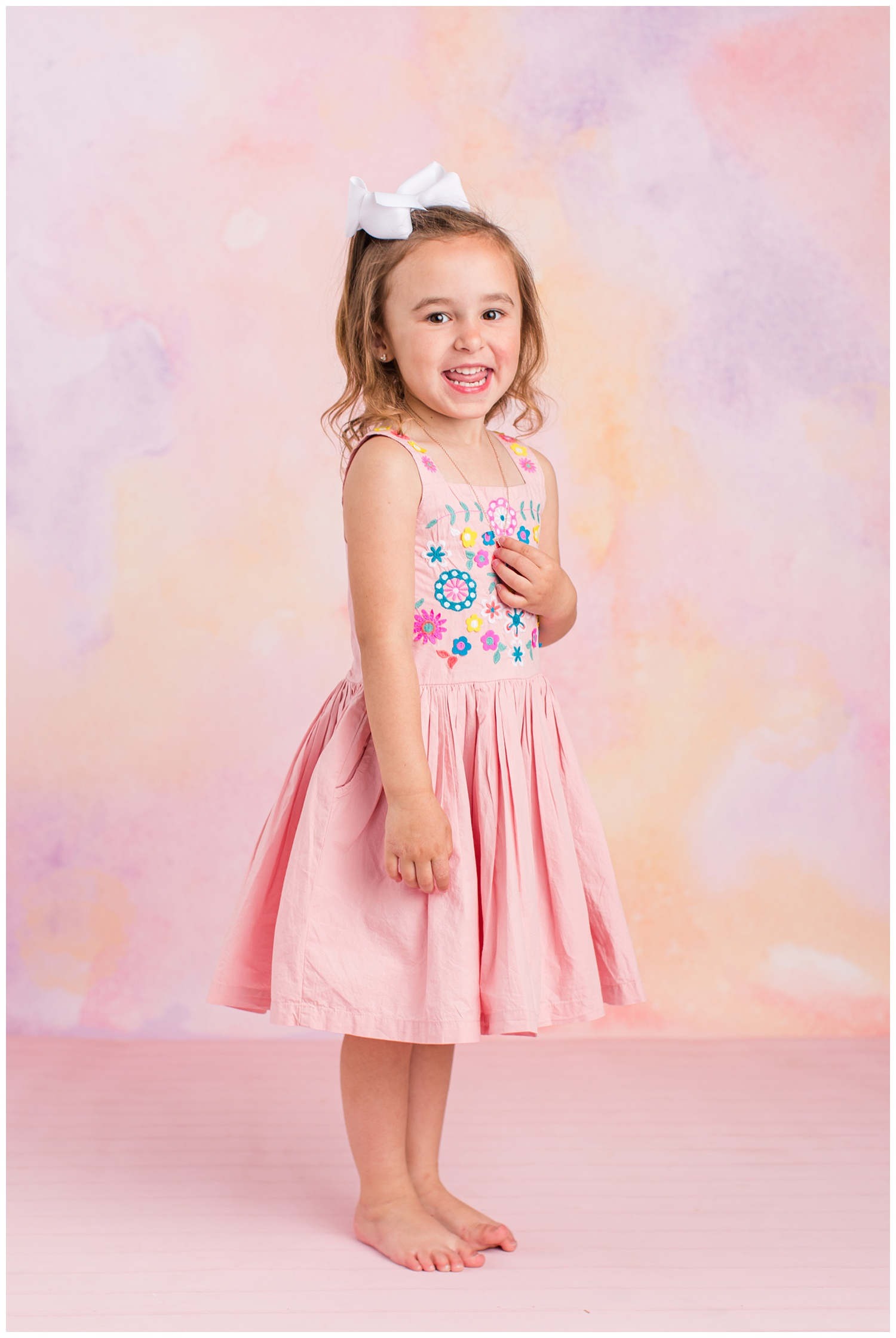 Four year old Sadie standing and smiling wearing a pink dress with floral embroidery on the bodice.