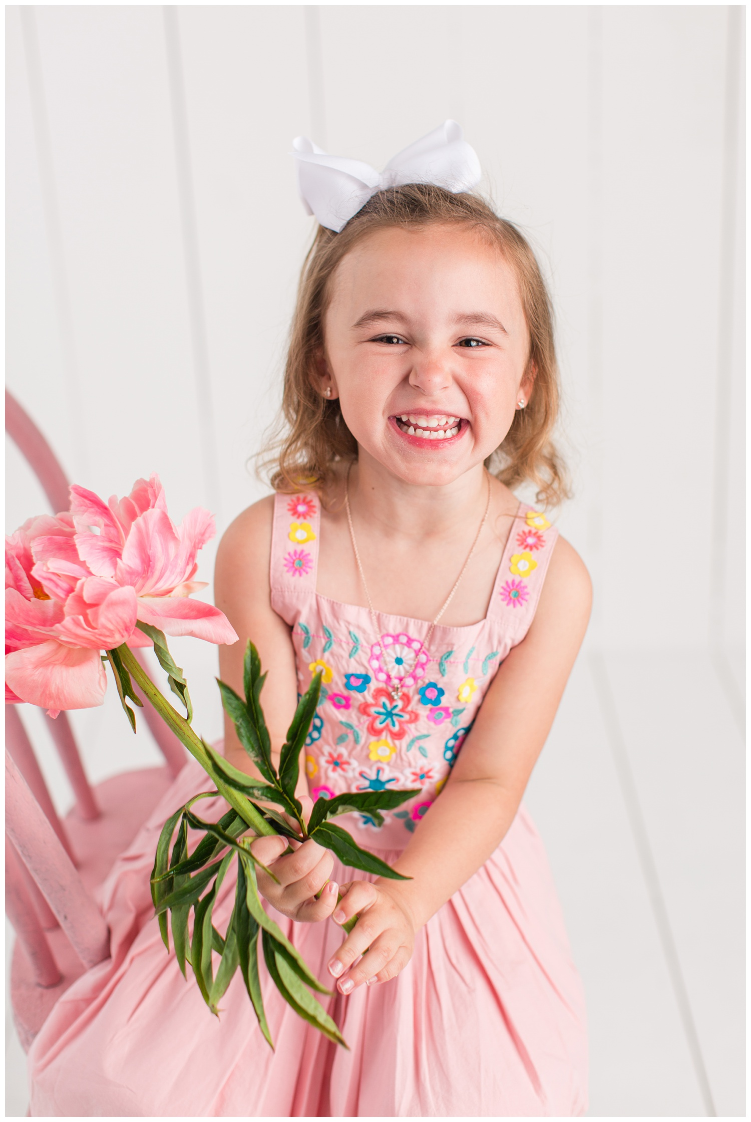 Four year old Sadie laughing while sitting on a pink chair wearing a pink dress with floral embroidered bodice and holding a pink peony stem.